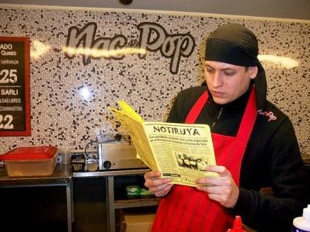 Alejandro, en Nac&Pop, cadena de locales de comidas rápidas en Buenos Aires, leyendo NOTIRUYA
